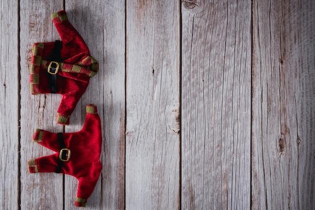 木製の背景にサンタクロースの服。スペースをコピーします。セレクティブフォーカス。