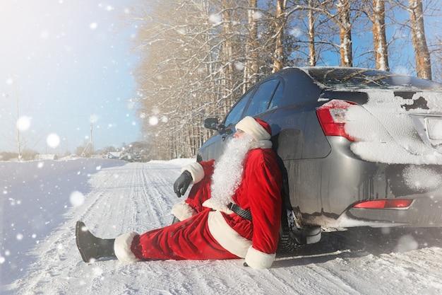 Дед мороз приходит с подарками с улицы. санта в красном костюме с бородой и в очках идет по дороге к рождеству. дед мороз приносит детям подарки.