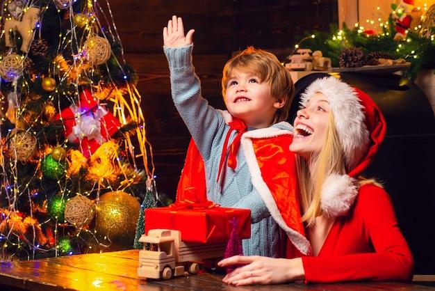 산타 클로스가 온다. 어머니와 어린 아이 소년 사랑스러운 친절한 가족 재미. 가족 집 크리스마스 트리에서 재미입니다. 엄마와 아이가 크리스마스 이브에 함께 놀아요. 행복한 가족. 가족 휴가.