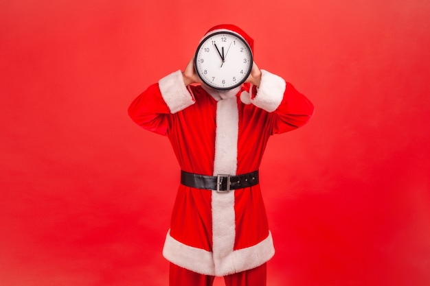 Santa claus covering face with wall clock, wasting his time, organization of working time.