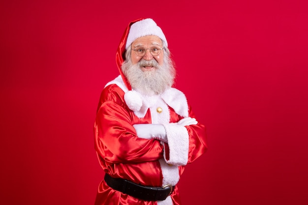 Santa claus crossed arms on red background. kind bearded santa claus with arms folded over red background. studio shot of realistic santa claus.