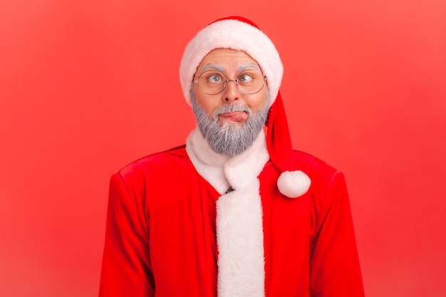 Santa claus crossing his eyes, tongue out, looking crazy and stupid, fooling around, having fun.