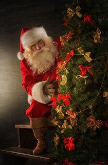 Дед мороз, украшающий елку в темной комнате