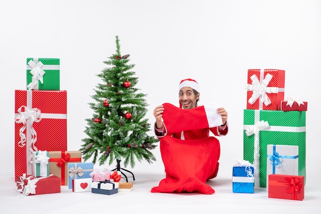 Santa claus in deep thoughts sitting with gift boxes and tree