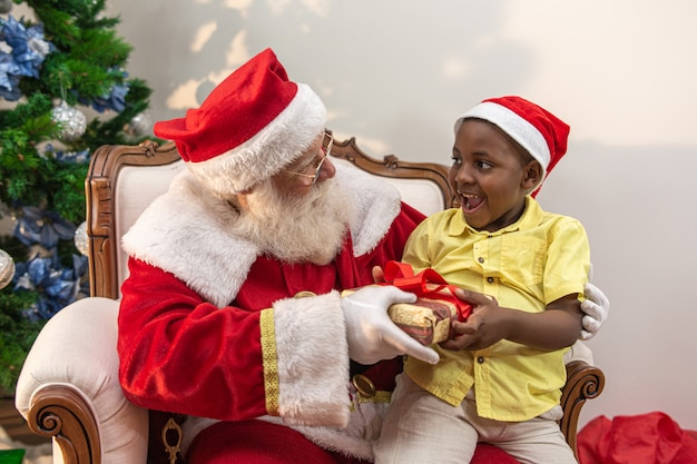 Santa claus delivering a gift box to a little african boy. hug