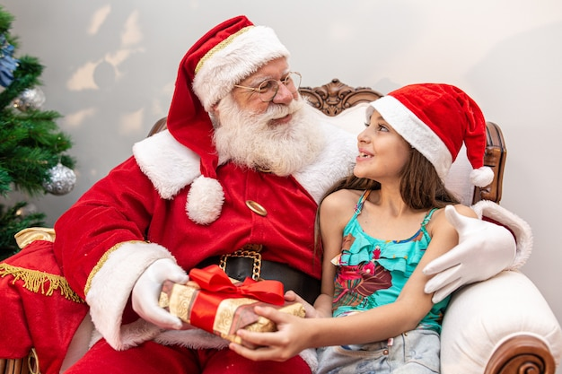 Santa claus delivering a gift box to a little girl
