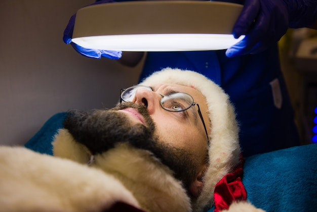 サンタクロースがスパクリニックで化粧品の手順を行います。スパクリニックでの化粧品の手順