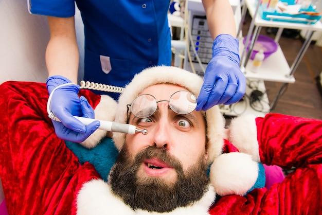 サンタクロースがスパクリニックで化粧品の手順を行います。