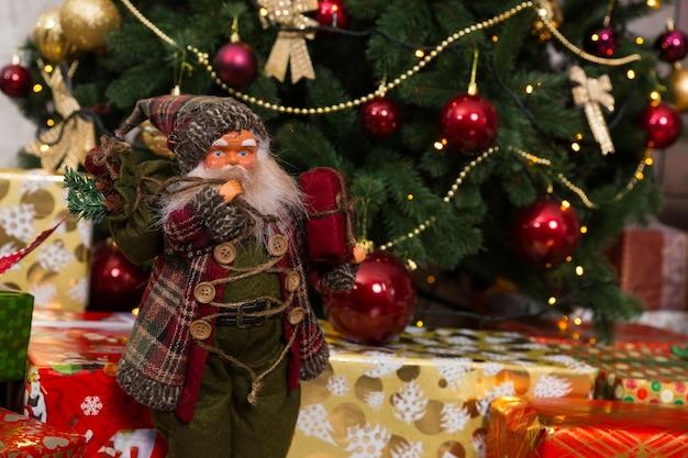 니트 의상을 입고 선물을 들고 크리스마스 트리 근처에 서 있는 선물을 들고 볼에 홍당무가 있는 산타 클로스 인형