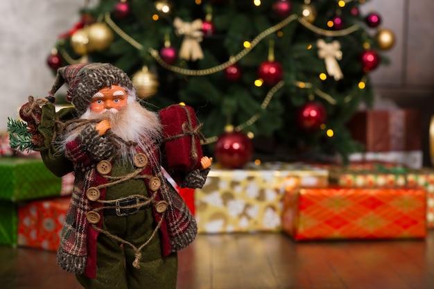전통 의상을 입고 크리스마스 트리 근처에 선물을 들고 있는 산타클로스 인형