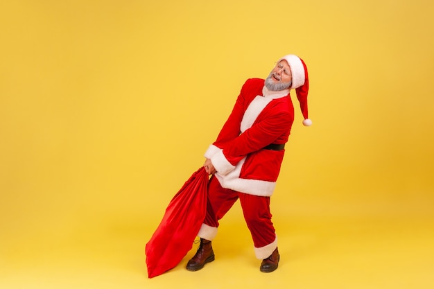 Santa claus dragging his large and heavy bag full of presents, frowning face, trying to lift up.