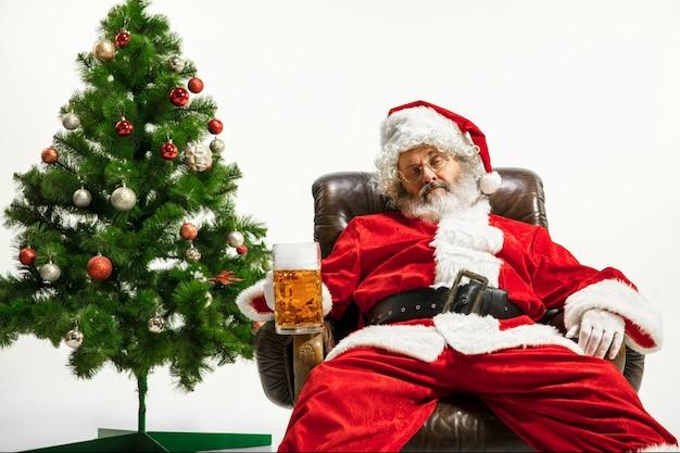 Санта-клаус пьет пиво возле елки, поздравляя, выглядит пьяным и счастливым
