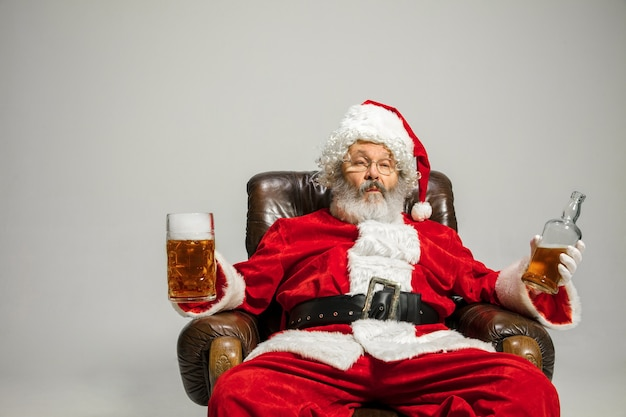 Санта-клаус пьет пиво, сидя на кресле, поздравляя, выглядит пьяным и счастливым. кавказская мужская модель в традиционном костюме. новый год 2020, подарки, праздники, зимнее настроение. copyspace для вашей рекламы.