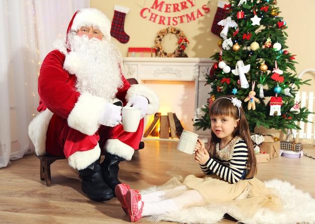 Санта-клаус пьет горячий шоколад с маленькой милой девочкой возле елки дома