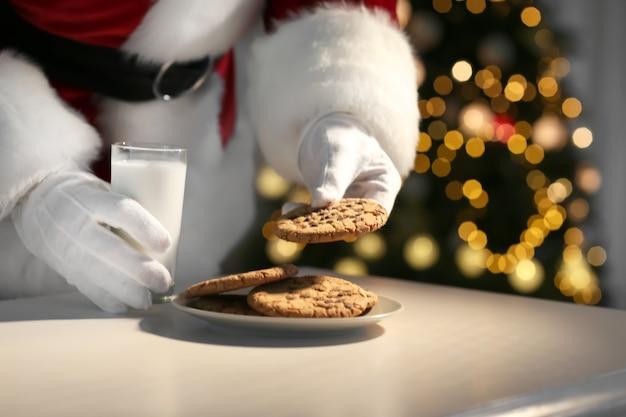サンタクロースがテーブルでクッキーを食べ、牛乳を飲む、クローズアップ