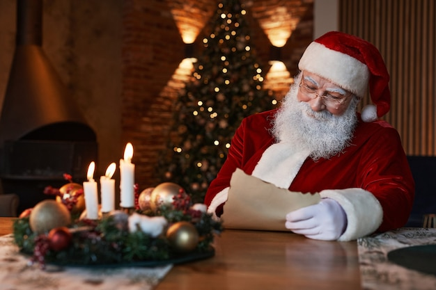 Santa claus in eyeglasses sitting at table with christmas cetrepiece and reading letter in dark cozy...