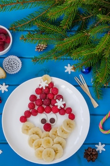 Santa claus face made of raspberries and banana with chocolate