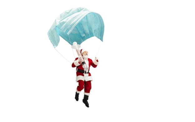 Covidに対するワクチンを与える気球のように巨大なフェイスマスクで飛んでいるサンタクロース