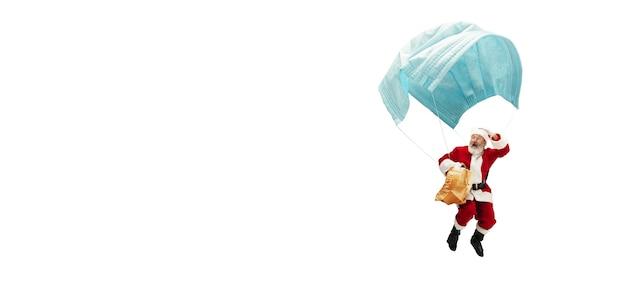 白い背景で隔離の気球のように巨大なフェイスマスクで飛んでいるサンタクロース。伝統的な衣装で白人男性モデル。新年、ギフト、休日、冬、covid、パンデミックの概念。コピースペース。