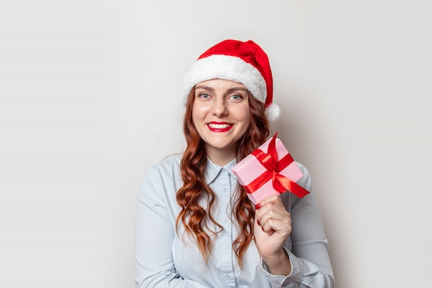 Santa claus girl with curly hair and a red hat with a bumbon holds a gift box with a red satin ribbon bow and smiles on a  of gray wall. merry christmas and new year web banner for site.