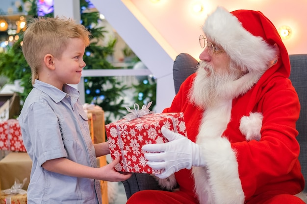 Santa claus gives boy a gift in shopping mall. real authentic santa talking and playing surprise