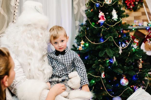 自宅のクリスマスツリーの近くの膝の上にいる小さなかわいい男の子にプレゼントを贈るサンタクロース。雪の乙女は子供たちに贈り物を持ってきました。新年のコンセプト。メリークリスマス。休日。