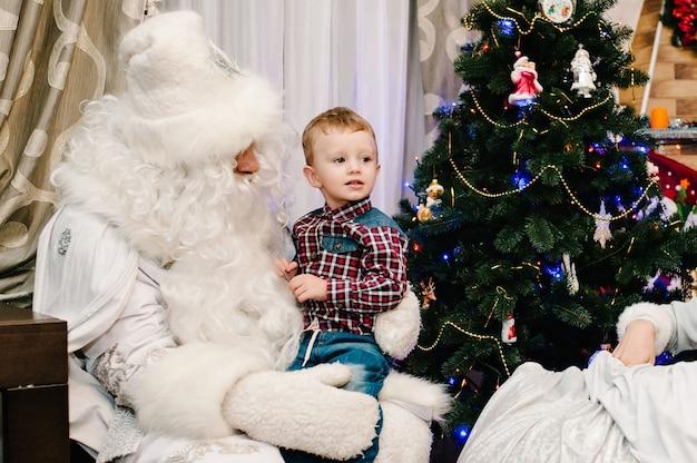 自宅のクリスマスツリーの近くの膝の上にいる小さなかわいい男の子にプレゼントを贈るサンタクロース。