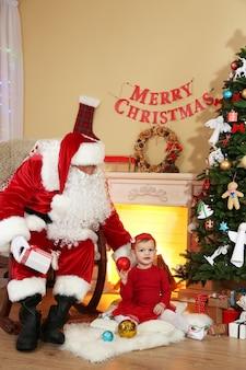 Санта-клаус дарит подарок маленькой милой девочке возле камина и елки дома