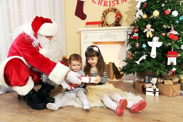 Санта-клаус дарит подарок маленьким симпатичным девочкам возле камина и елки дома