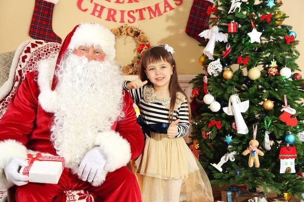 Санта-клаус дарит подарок спящей маленькой милой девочке у себя дома на елке