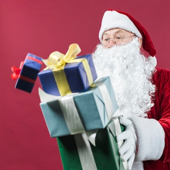 Santa claus in glasses dropping gift boxes