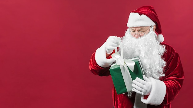 Santa claus in glasses holding green gift box