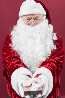 Santa claus in glasses holding small gift box