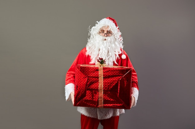Santa claus in glasses holds in his hand the huge christmas present on the gray background. .