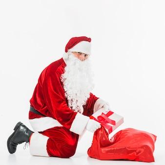 Santa claus in glasses putting gift box in sack