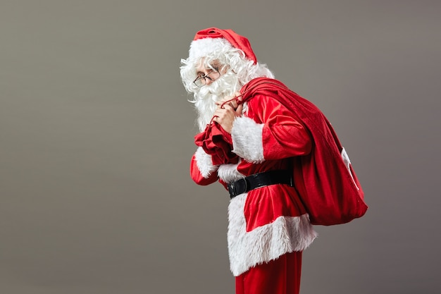 Santa claus in glasses stands with the bag with christmas gifts on his back on the gray background .