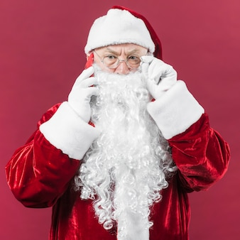 Santa claus in glasses talking by phone