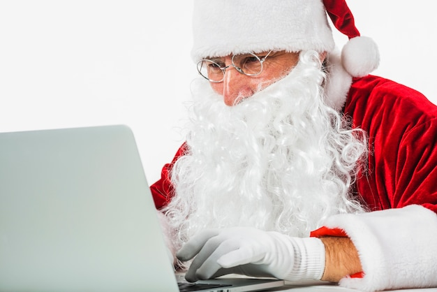 Santa claus in glasses using laptop
