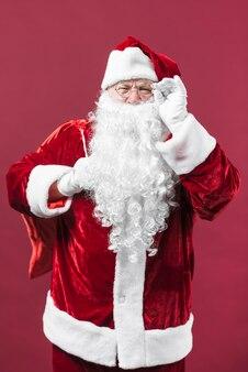 Santa claus in glasses with big sack behind back