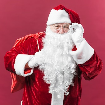 Santa claus in glasses with sack behind back