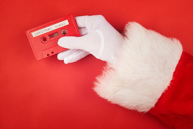 Santa claus hand holding an audio cassette tape with christmas songs recorded
