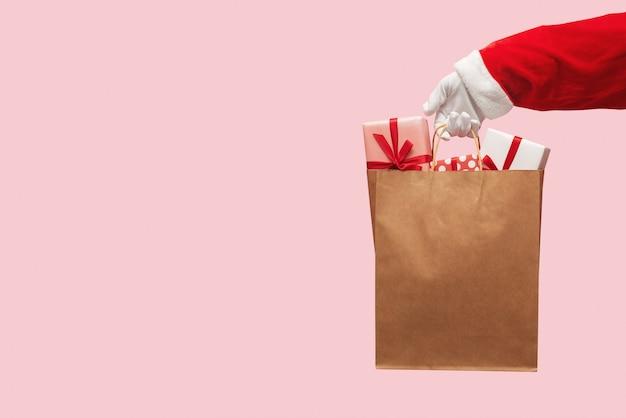 산타 클로스 손을 잡고 선물 상자와 갈색 쇼핑백