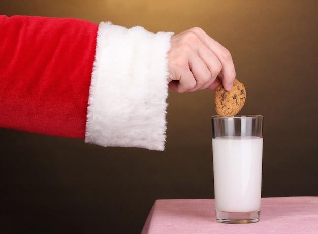 茶色の表面にチョコレートクッキーを持っているサンタクロースの手