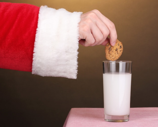 チョコレートクッキーを持っているサンタクロースの手