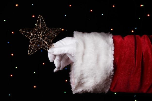 明るい表面にクリスマスの星を持っているサンタクロースの手