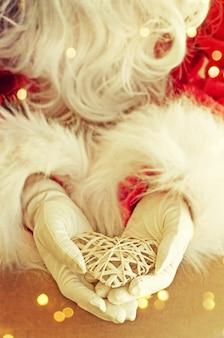 Santa claus hand holding heart