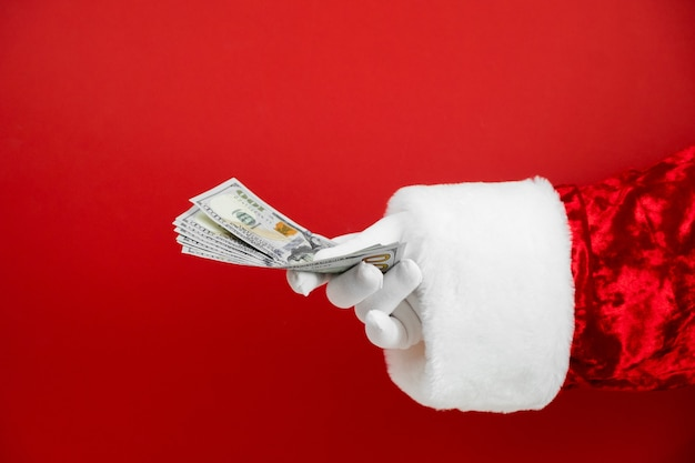 Santa claus hand holding money on red