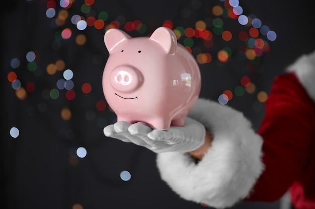 돼지 저금통을 들고 산타 클로스 손
