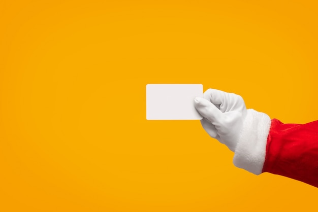 Santa claus hand holding plastic credit card over isolated.