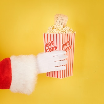 Santa claus hand holding a red and white bucket with popcorn